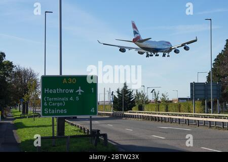 British Airways Boeing 747 landing at London Heathrow Airport over a motorway with a sign to the airport in the foreground. - Stock Photo