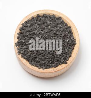 Close-up view of raw black cumins in a small wooden bowl on white background.