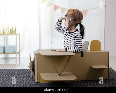 Asian little child girl playing with cardboard toy airplane handicraft isolated in home with copy space for your text, Creative with family and dreami