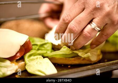 Preparing fresh tasty cheese burgers, closeup of woman hands. - Stock Photo
