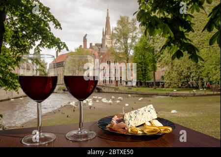 Two glasses of wine with charcuterie assortment on view of Bruges, Belgium. Glass of red wine with different snacks - plate with ham, sliced - Stock Photo