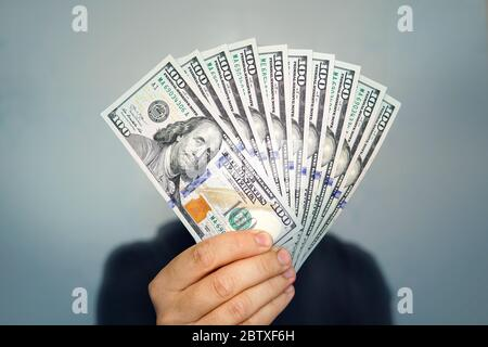 1000 dollars in 100 bills in a man's hand close-up on a dark background. Hands holding dollar cash