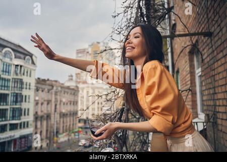 Cheerful lady standing on balcony and greeting friend