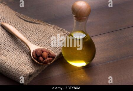 Almond oil in bottles Place side by side with an almond seed on a sack bag with a wooden background - Stock Photo