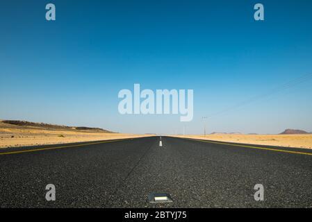 A long straight road leading through dessert - Stock Photo
