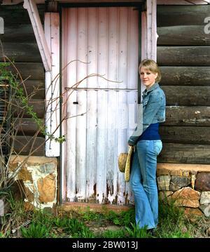 Young woman leans against a rustic log house that has a pink door.  She is wearing jeans and denim jacket.  She is holding a straw hat. - Stock Photo