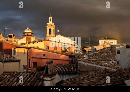 Rooftops of Foligno caught in sunlight, but set against stormy sky with a rainbow.  Umbria, Italy - Stock Photo