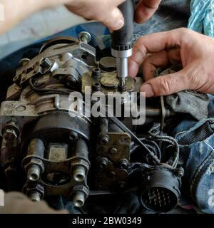 A mechanic disassembles and detects a fuel injection pump. The process of repairing the fuel pump of a diesel car in the workshop. Car service. Select - Stock Photo