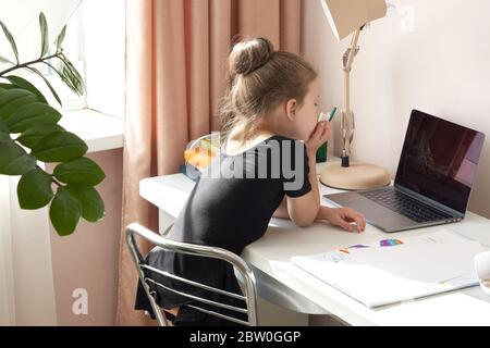 Curious little girl using laptop at desk