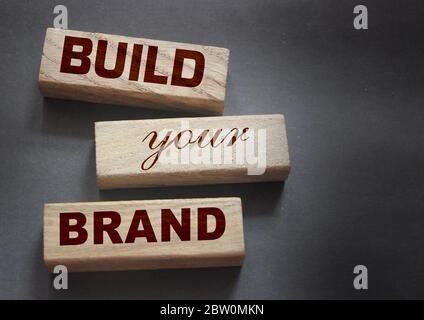 Phrase BUILD YOUR BRAND written on wooden blocks. With vintage styled background. Branding rebranding marketing concept