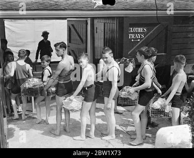 Long queue at Hammersmith open-air baths eight wave refuges. Hundreds of people sought refuge from the heat at the Hammersmith open-air baths. A long queue waited for admission throughout the afternoon. Photo show, bathers with their clothes baskets at the Hammersmith Baths. 29 May 1937 - Stock Photo
