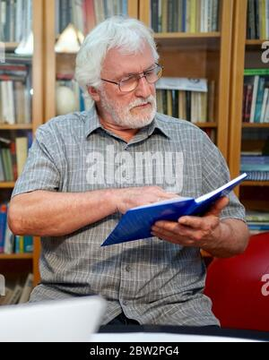 Portrait of a white bearded senior man with grey shirt reading a blue notebook, book while sitting in front of a huge book shelf in the background.