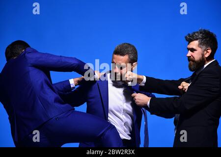 Rivalry and business confrontation concept. Coworkers decide upon best working position. Businessmen with strict faces in formal wear on blue background. Company leaders fight for business leadership - Stock Photo