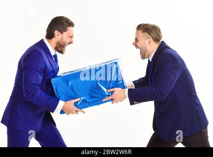 Business rivalry concept. Men or businessmen with mad faces take away from each other package, isolated on white background. Two businessmen with aggressive expression pull box in opposite directions. - Stock Photo
