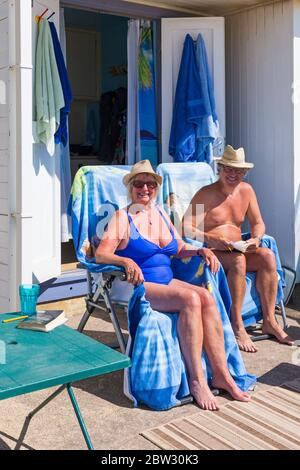 Bournemouth, Dorset UK. 29th May 2020. UK weather: another lovely warm sunny day at Bournemouth beaches with a bit of a breeze, as the glorious weather continues and temperatures rise. Sunseekers head to the seaside to enjoy the sunshine. Sue and Rob soak up the sun rays at their beach hut. Credit: Carolyn Jenkins/Alamy Live News - Stock Photo