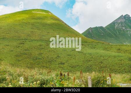 A grassy hill with the word 'Gudauri' arranged from white painted rocks at the top, opposite the Gudauri Viewpoint, Mtskheta-Mtianeti region, Georgia - Stock Photo