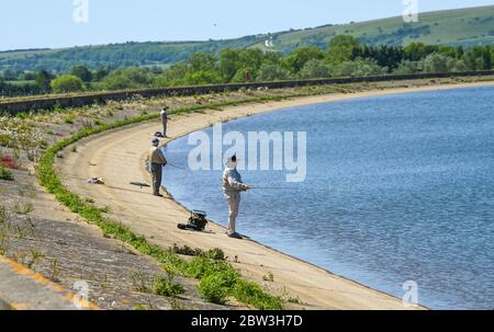 Eastbourne UK 29th May 2020 - Fishermen at Arlington Reservoir near Eastbourne in Sussex on a hot sunny day during the Coronavirus COVID-19 pandemic crisis  . Credit: Simon Dack / Alamy Live News - Stock Photo