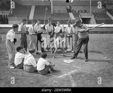 A Hundred London Boys Learn How To Play Baseball At The White City To discover young baseball talent , a hundred boys turned out for tuition at the White City Stadium under the guidance of  Doc  Hayden , the American manager - coach . Small - sized baseball gloves were provided , and the boys received instruction in fieldinf , pitching and batting . Boys who show the highest promise will play next year in a new juniour league . Photo shows :  Doc  Hayden showing the boys how to strike . 17 Aug 1936 - Stock Photo