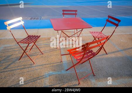 café outdoor dining, red table and chairs. - Stock Photo
