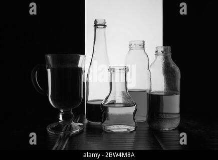 bottled on a light background with liquid black and white silhouette photo - Stock Photo