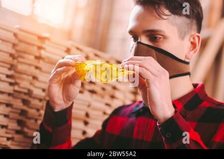 Closeup of male carpenter in protective face mask wearing eye protection glasses while working at wood production workshop. Man cabinet maker holding - Stock Photo