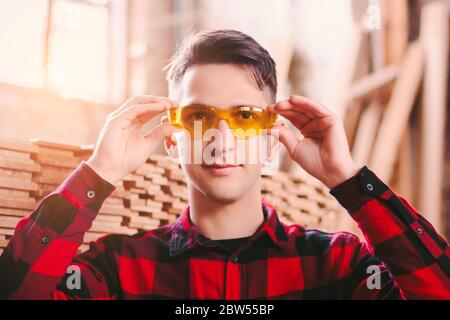 Happy man cabinet maker wearing protective glasses and smiling while working at sawmill factory. Young male carpenter hold eyewear protection at woodw - Stock Photo