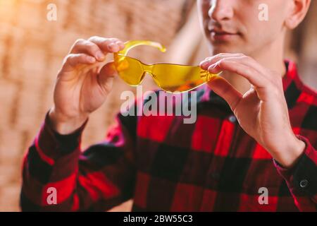 Closeup of man professional carpenter holding protective glasses in hands while working at woodworking workshop. Male cabinet maker wearing eye protec - Stock Photo
