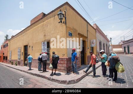 People line up to receive free food served by the community kitchens during the coronavirus crisis.Several economic canteens in conjunction with civil associations have been given the task of giving food to people who need it in times of coronavirus pandemic. Credit: SOPA Images Limited/Alamy Live News - Stock Photo