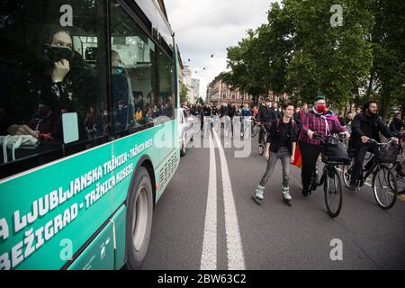 Ljubljana, Slovenia. 29th May, 2020. Passengers in a bus watch protesters on bicycles ride by during the demonstration.Every Friday, thousands of people in Ljubljana protest against the government of Prime Minister Janez Janša amid allegations of his government's corruption and undemocratic rule. Credit: SOPA Images Limited/Alamy Live News - Stock Photo