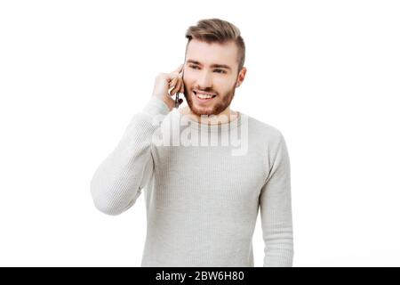 Cheerful young man talking on the phone isolated - Stock Photo
