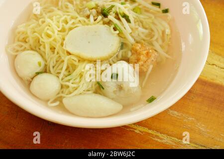 Chinese egg noodles topping fish dumpling and shrimp ball in clear soup on bowl - Stock Photo