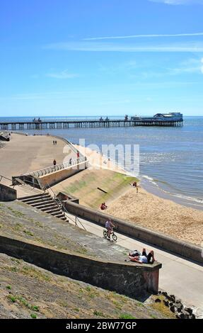 People on the beach and seawall next to North Pier relaxing on a hot summer day in Blackpool - Stock Photo