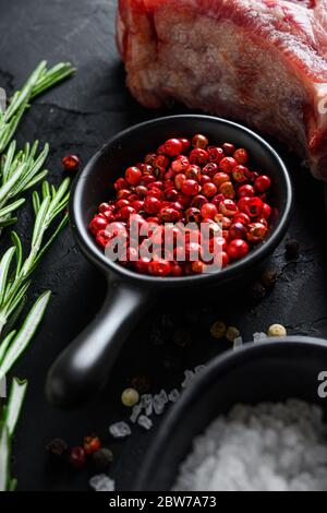 Rose Peppercorn and Rosemary herbs close up on black stone table with spices and raw meat near side view selective focus vertical - Stock Photo