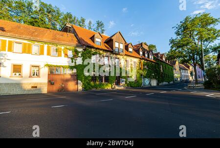 A small hotel on the street. Ivy-covered walls. City tour. A charming place to stay. Evening in the city. Entrance from the street. The facade is cove - Stock Photo