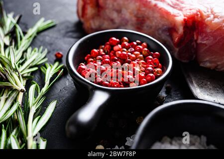 Rose Peppercorn and Rosemary herbs close up on black stone table with spices and raw meat nea rside view selective focus. - Stock Photo