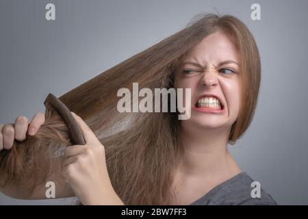 Young caucasian woman girl struggling to comb brush her straight hair with funny frustrated face. Long hair problem concept - Stock Photo