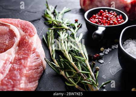 Rosemary herbs close up on black stone table with spices and raw meat near side view selective focus. - Stock Photo