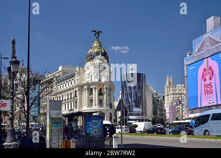 MADRID / SPAIN - APRIL 12, 2019 - Metropolis, one of the most beautiful buildings in the Calle de Alcala street with traffic jam in Madrid, Spain - Stock Photo