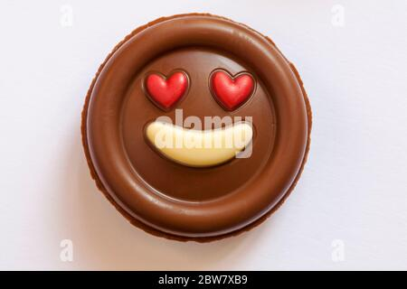 M&S Milk Chocolate Emotions - put a smile on your face chocolate removed from pack isolated on white background - red heart eyes love emoji emoticon - Stock Photo