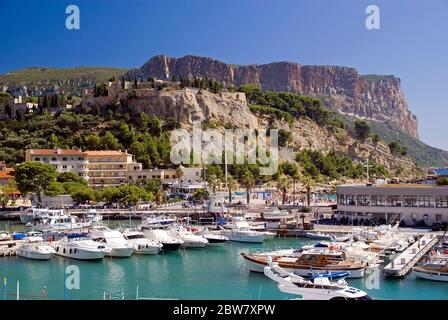 The fishing village of Cassis in Provence: the harbour and the distant cliffs of Cap Canaille - Stock Photo