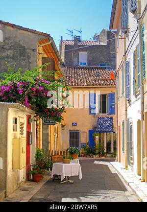 The fishing village of Cassis in Provence: a narrow back-street with a table for one. - Stock Photo