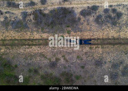 Couple lying on a rail track drone aerial top view on a desert landscape - Stock Photo