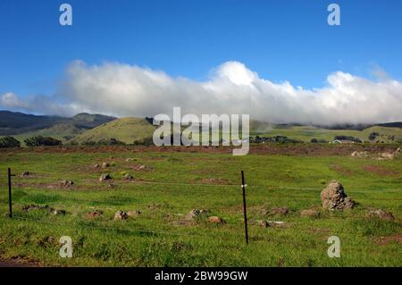 Upcountry on the Big Island is filled with grass covered cinder cones of long cold volcanos.  Misty clouds and blue skies cover Kohala Mountains in Ha - Stock Photo