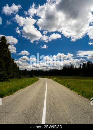 Countryside countryroad sunshine with numerous Spring clouds Sunger in Croatia Europe centered center stripe White line