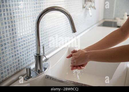 Woman washing her hands with soap, corona virus pandemic, covid-19 - Stock Photo