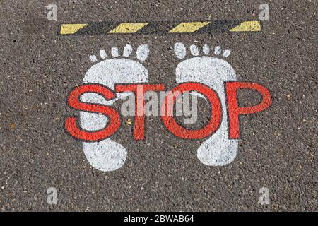 Poole, Dorset UK. 31st May 2020. Stop sign with footprints on pavement at Poole - pavement markings. Credit: Carolyn Jenkins/Alamy Live News - Stock Photo