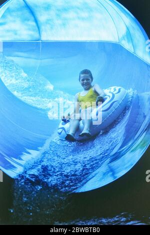 A youngster riding the Water flume ride at Sunsplash Waterworld, Somerwest World, a Butlins Holday camp in Minehead. Somerset. England, UK. Circa 1980's - Stock Photo