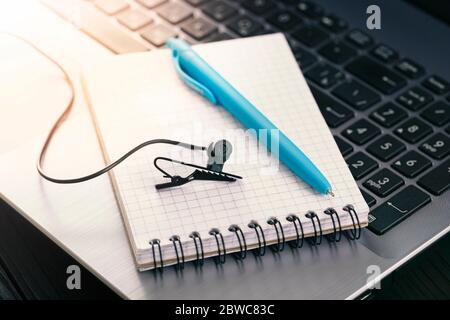 Concept for online conference, stream, webinar. Wired Microphone, notepad and laptop are prepared for video communication over the Internet - Stock Photo
