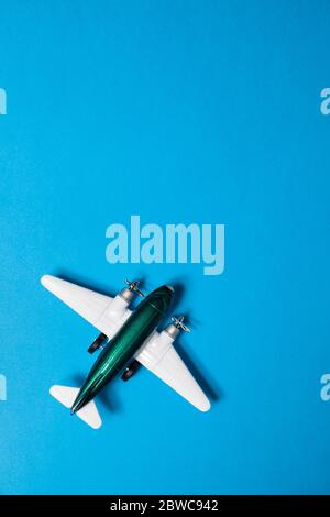 Miniature toy airplane with copy space on blue background - Stock Photo