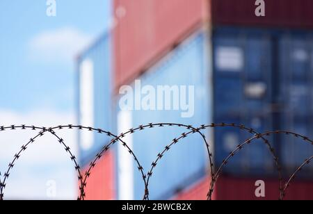 Freight shipping containers stacked up behind barbed wire at a busy European sea port